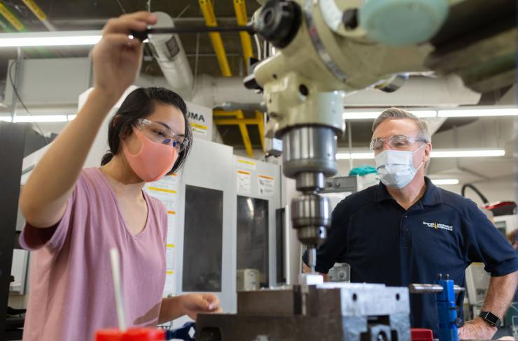 Steven Sheffield, machine shop manager, works with Gwen Wang, mechanical engineering doctoral student, in the Montgomery Machining Mall. (Photo by Allison Carter.)